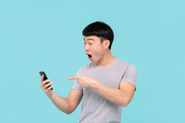 Schockierter aufgeregter junger asiatischer mann, der nach luft schnappt und auf handy zeigt