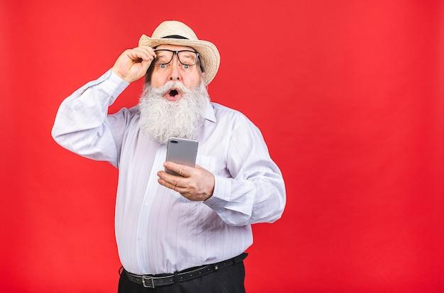 Schockierter bärtiger alter mann mit hut und brille, die ein handy lokalisiert auf rotem hintergrund halten