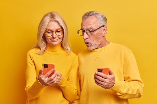 Schockierter bärtiger alter mann starrt auf modernes smartphone-gerät, das zeigt, dass frau moderne geräte benutzt, um schockierende nachrichten im internet zu lesen, isoliert über gelber wand