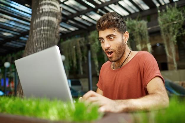 Schockierter bärtiger junger mann mit dunklem haar und aufgesprungenen augen, geöffneter mund in rotem t-shirt mit blick auf den bildschirm seines notizbuchs