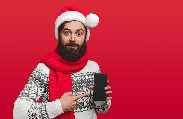 Schockierter bärtiger kerl in der weihnachtsmütze, die auf app leeren bildschirm zeigt