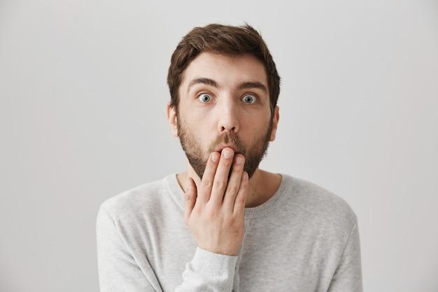 Schockierter bärtiger mann bedeckt den mund, als er erstaunliche gerüchte hört