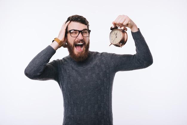 Schockierter bärtiger mann im pullover, der wecker schaut