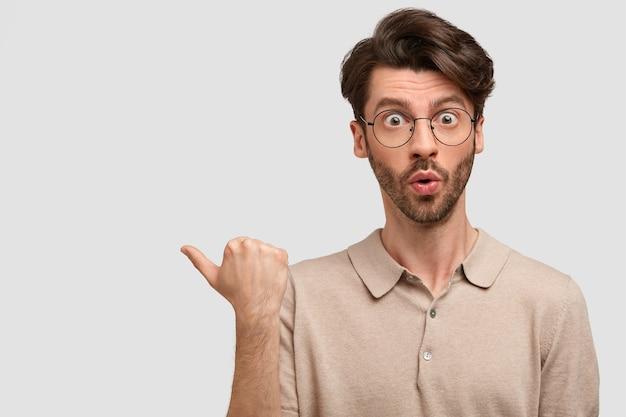Schockierter bärtiger mann mit verblüfftem gesichtsausdruck, zeigt mit dem daumen zur seite