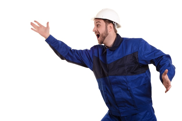 Schockierter bauingenieur in einem schützenden weißen helm und einer blauen uniform