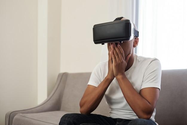 Schockierter emotionaler junger schwarzer mann, der videospiel spielt oder video in gläsern sieht