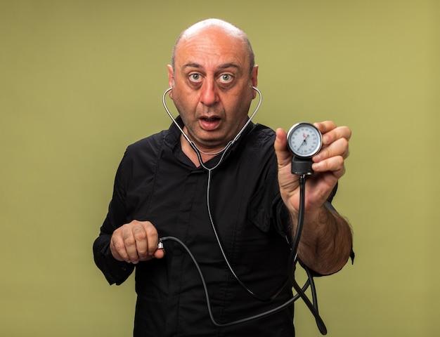 Schockierter erwachsener kranker kaukasischer mann, der blutdruckmessgerät lokalisiert auf olivgrüner wand mit kopienraum hält