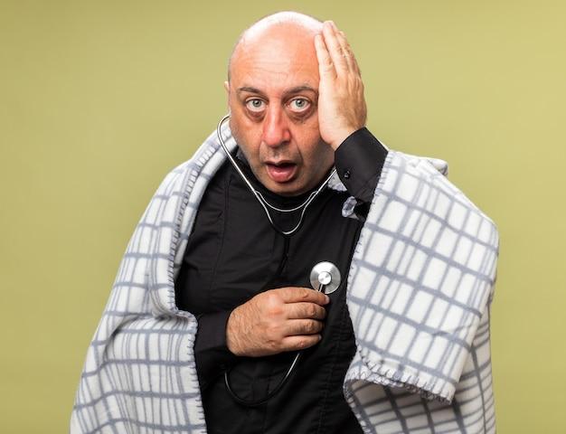 Schockierter erwachsener kranker kaukasischer mann, der in plaid gewickelt ist, legt hand auf kopf, der herzschlag mit stethoskop misst, das auf olivgrüner wand mit kopienraum isoliert wird