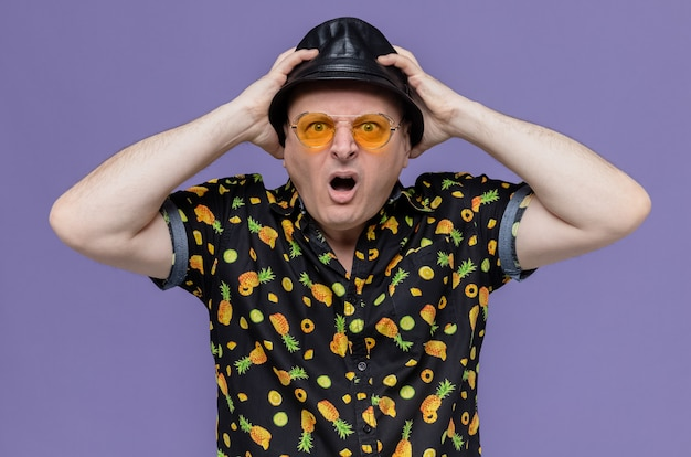 Schockierter erwachsener mann mit schwarzem hut mit sonnenbrille, der hände auf seinen hut legt und schaut