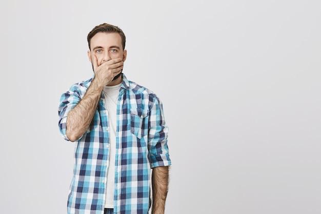 Schockierter erwachsener mann schnappt nach luft, bedeckt den mund mit der hand