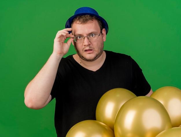 Schockierter erwachsener slawischer mann hält und schaut durch eine optische brille auf die kamera, die einen blauen partyhut trägt, der mit heliumballons steht