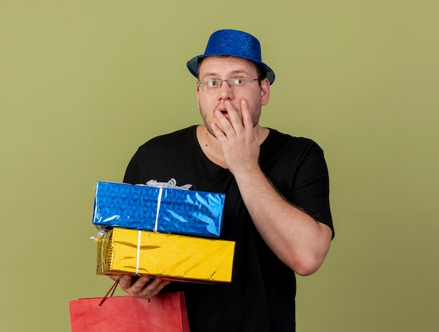 Schockierter erwachsener slawischer mann in optischer brille mit blauem partyhut legt die hand auf das gesicht und hält geschenkboxen und papiereinkaufstasche