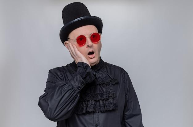 Schockierter erwachsener slawischer mann mit hut und sonnenbrille in schwarzem gothic-hemd, der die hand auf sein gesicht legt und zur seite schaut