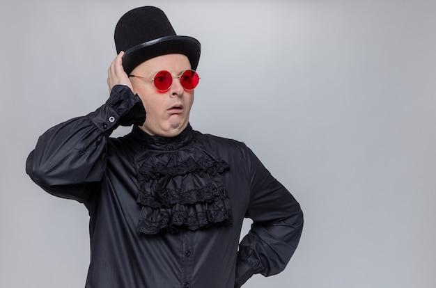 Schockierter erwachsener slawischer mann mit zylinder und sonnenbrille in schwarzem gothic-hemd, der auf die seite schaut