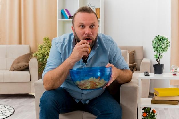 Schockierter erwachsener slawischer mann sitzt auf sessel, der schüssel des chips innerhalb des wohnzimmers hält und isst