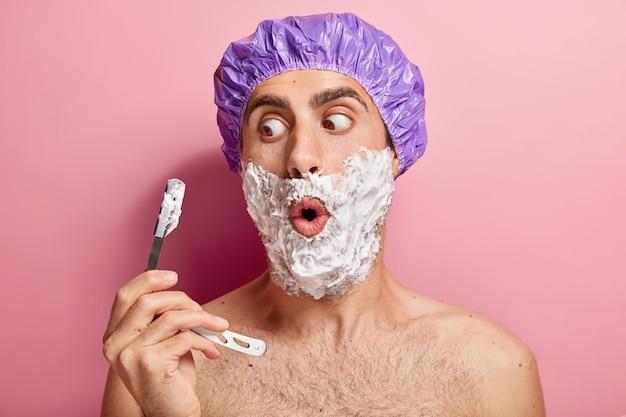 Schockierter europäischer mann hält rasierklinge, trägt schaumgel auf die wangen auf, rasiert borsten, trägt lila schutzduschhaube, hat hygieneroutine