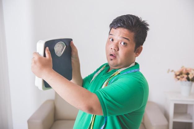 Schockierter fettleibiger mann beim betrachten einer waage
