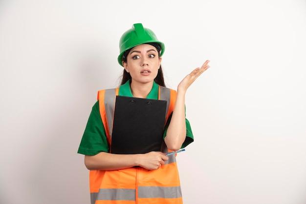 Schockierter frauenkonstrukteur mit grünem helm, der mit zwischenablage steht. foto in hoher qualität