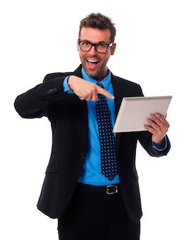 Schockierter geschäftsmann, der auf digitalem tablett zeigt
