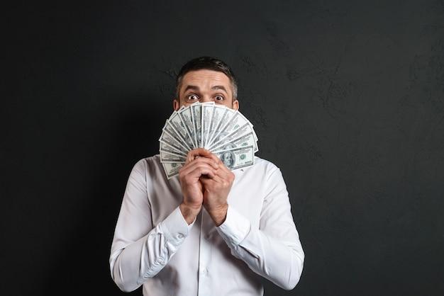 Schockierter geschäftsmann, der gesicht mit geld bedeckt.