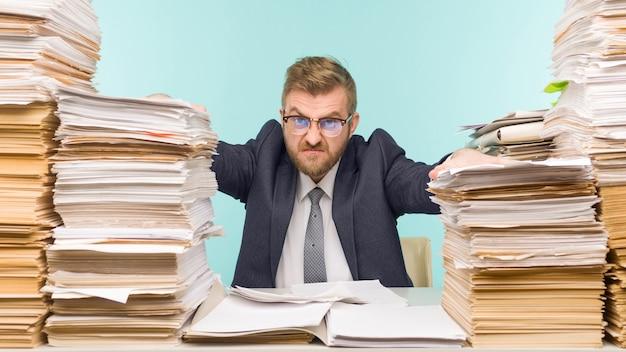 Schockierter geschäftsmann, der mit vielen papieren im büro am tisch sitzt, ist überladen mit arbeitsbildern