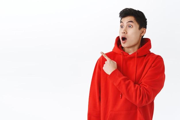 Schockierter, gutaussehender, erschrockener asiatischer mann, der nach luft schnappt, den kiefer fallen lässt und auf etwas tolles starrt, mit dem finger beeindruckt, sprachlos über ein cooles ereignis, eine stehende weiße wand.