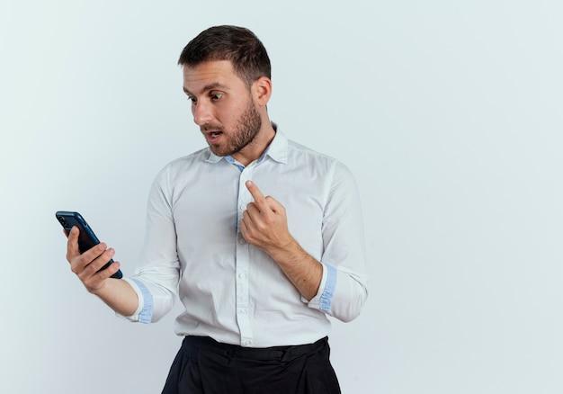 Schockierter gutaussehender mann hält und schaut auf telefon, das isoliert auf weißer wand zeigt