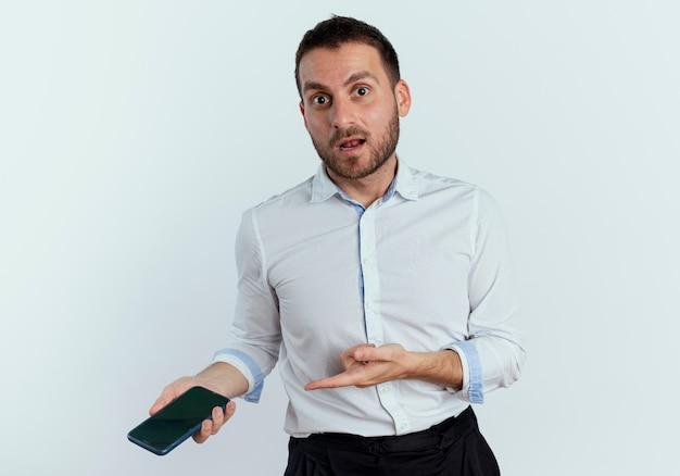 Schockierter gutaussehender mann hält und zeigt auf telefon, das isoliert auf weißer wand schaut
