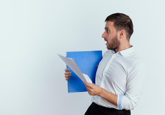 Schockierter gutaussehender mann steht seitwärts und hält aktenordner und papierblätter isoliert auf weißer wand