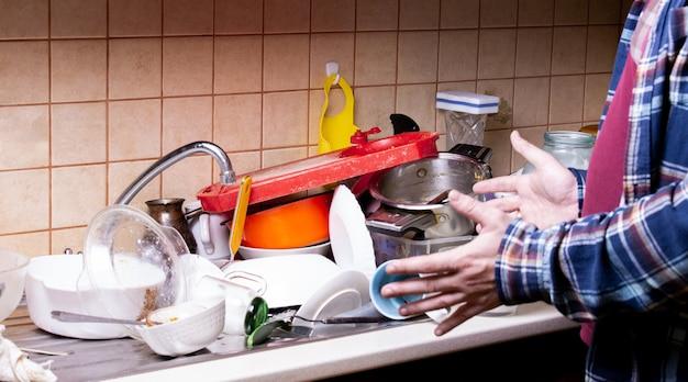 Schockierter handkerl nahe vielen schmutzigen tellern, die in der wanne in der küche liegen, die sie waschen möchten