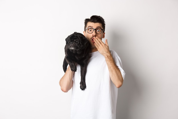 Schockierter hundebesitzer, der in die kamera starrt, den welpen auf der schulter hält und erstaunt nach luft schnappt. hübscher junger mann trägt mops und reagiert auf promo-werbung, weißer hintergrund.