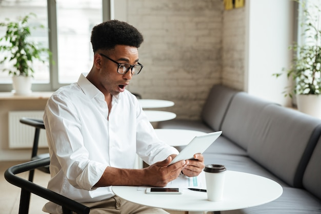 Schockierter junger afrikanischer mann, der coworking sitzt