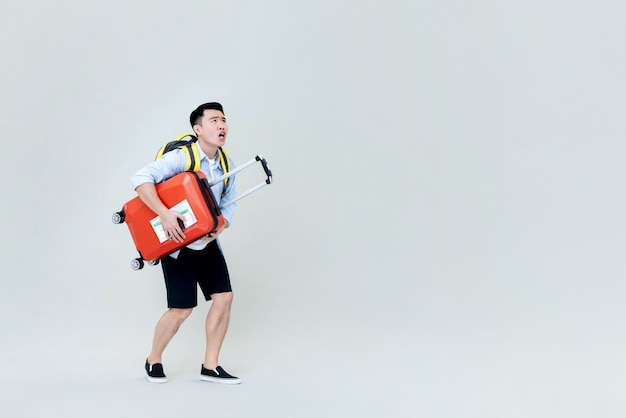 Schockierter junger asiatischer mann-tourist mit gepäck, das nach oben schaut