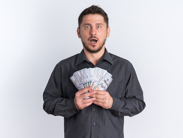 Schockierter junger blonder gutaussehender mann, der geld mit offenem mund hält und in die kamera schaut