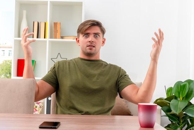 Schockierter junger blonder gutaussehender mann sitzt am tisch mit telefon und tasse, die hände heben und kamera im wohnzimmer betrachten