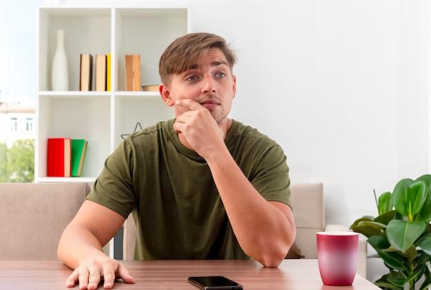 Schockierter junger blonder gutaussehender mann sitzt am tisch mit telefon und tasse, die kinn halten und seite im wohnzimmer betrachten