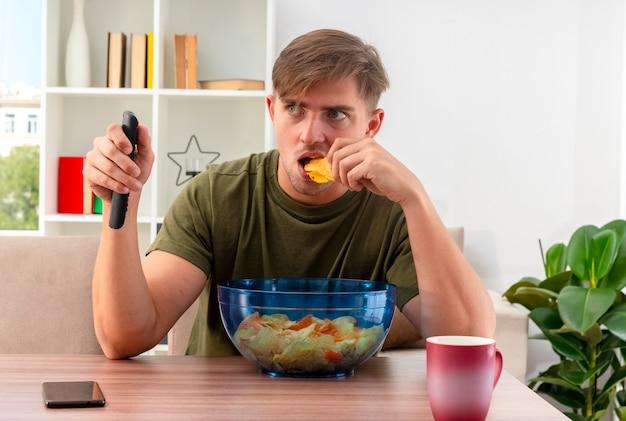 Schockierter junger blonder gutaussehender mann sitzt am tisch mit telefonschüssel chips und tasse, die tv-fernbedienung hält und chips innerhalb des wohnzimmers isst