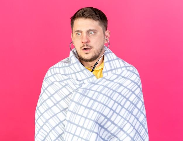 Schockierter junger blonder kranker mann gewickelt in kariertem messdruck mit blutdruckmessgerät lokalisiert auf rosa wand
