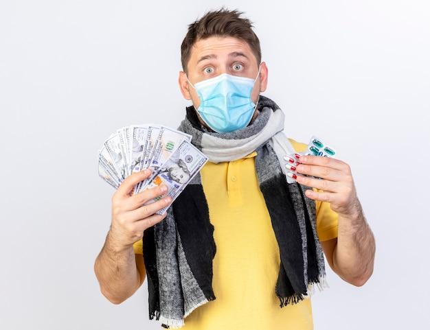 Schockierter junger blonder kranker slawischer mann, der medizinische maske und schal trägt, hält geld und packungen von medizinischen pillen, die auf weißer wand mit kopienraum isoliert werden