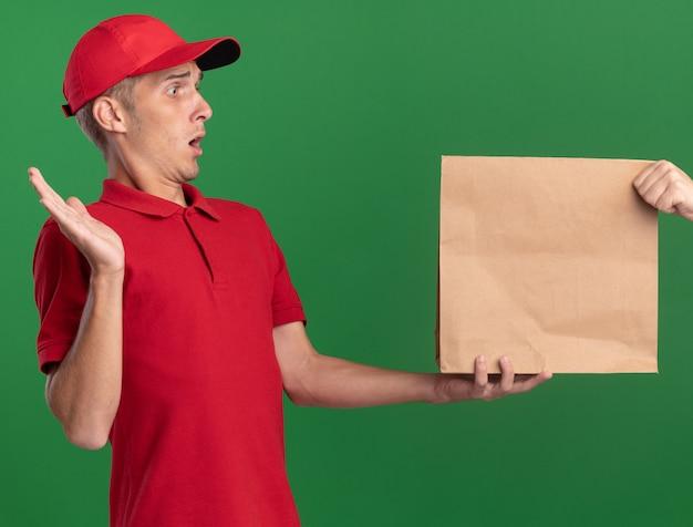Schockierter junger blonder lieferjunge steht mit erhobener hand und nimmt papierpaket auf grün