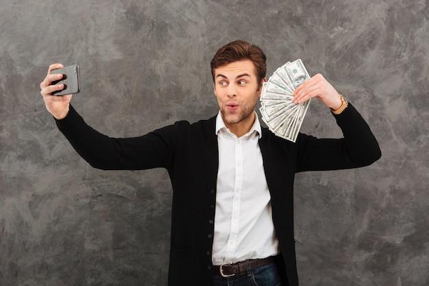 Schockierter junger geschäftsmann, der geld hält, macht selfie per handy.