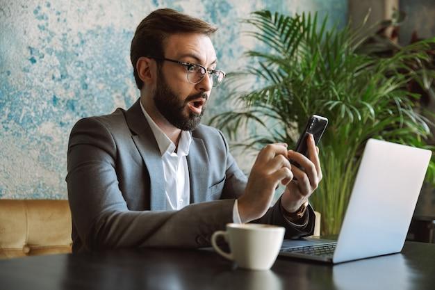 Schockierter junger geschäftsmann im anzug, der an einem laptop arbeitet, drinnen im café sitzt und handy hält