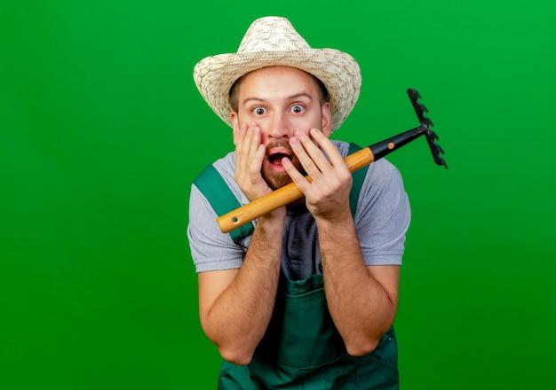 Schockierter junger hübscher slawischer gärtner in der uniform und im hut, der rechen hält, der hände auf gesicht lokalisiert auf grüner wand mit kopienraum hält