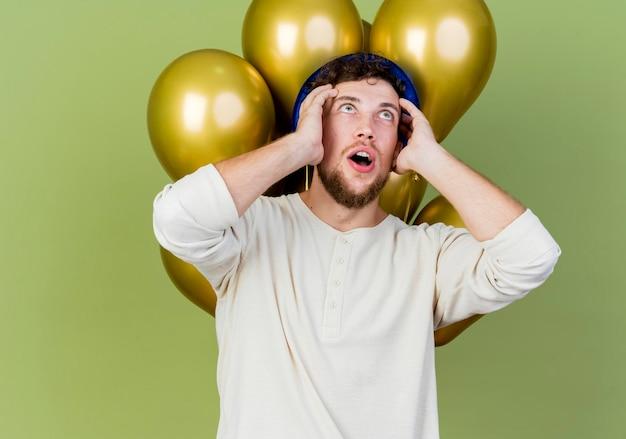 Schockierter junger hübscher slawischer party-typ, der partyhut trägt, der vor ballons steht, die den kopf berühren, der lokal auf olivgrüner wand mit kopienraum schaut