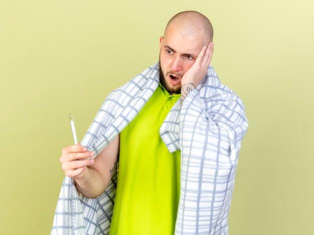Schockierter junger kranker mann, der in plaid gewickelt ist, legt hand auf gesicht, das thermometer hält und auf olivgrüne wand isoliert betrachtet