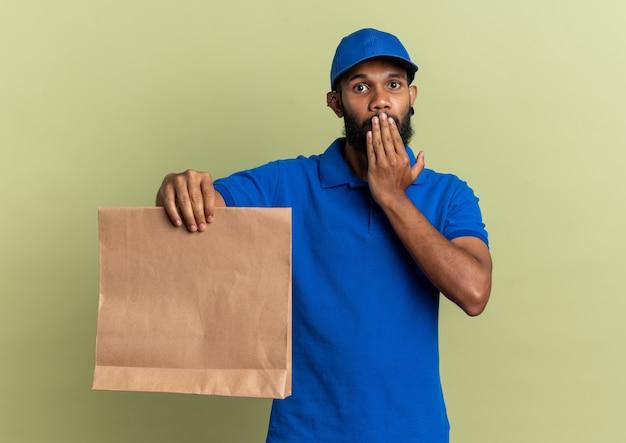 Schockierter junger lieferer, der die hand auf den mund legt und das lebensmittelpaket isoliert auf einer olivgrünen wand mit kopienraum hält?