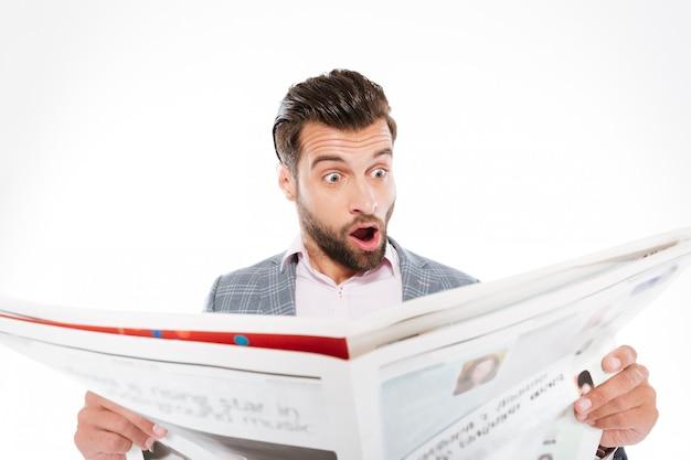 Schockierter junger mann, der gazette liest.