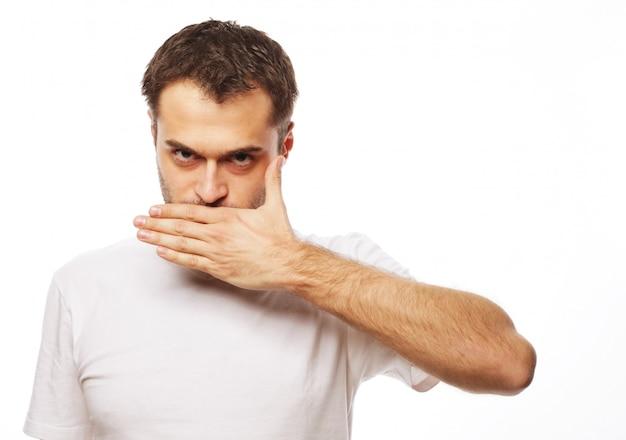 Schockierter junger mann, der mund mit händen bedeckt