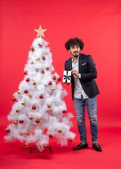 Schockierter junger mann, der sein geschenk hält, das nahe geschmücktem weißem weihnachtsbaum auf der rechten seite von rot steht