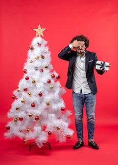 Schockierter junger mann, der sein geschenk hält und sein auge schließt, das nahe geschmücktem weißem weihnachtsbaum auf der rechten seite von rot steht